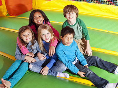 Multi-ethnic group of children (ages 7 to 10 years) in inflatable bouncy castle.